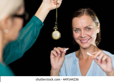Hypnotherapist holding pendulum by patient against black background