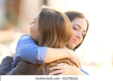 Hypocritical girl embracing a friend outdoors in the street