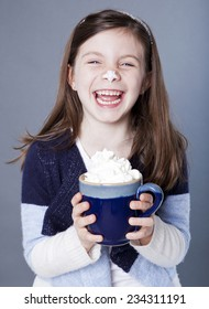 Hysterical little girl with a mug of hot cocoa and whipped cream on her nose
