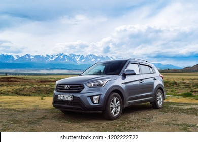 Hyundai creta ix25 on the field against the snowy peaks of the North-Chuya Range in the south-eastern part of the Altai Republic.  Russia, Altai Republic. July 2018