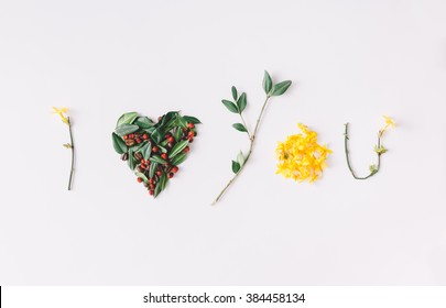 """""""I heart you"""" made of flowers, leaves, berries and coffe beans."""