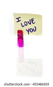 """""""I love you"""" message written on a yellow paper note with a clothespins holding isolated on white background with reflections."""