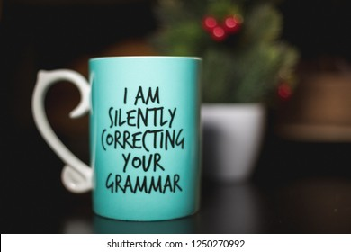 """I am silently correcting your grammar"" coffee mug for comedy and education purposes. Turquoise mug on black ground with cozy background."