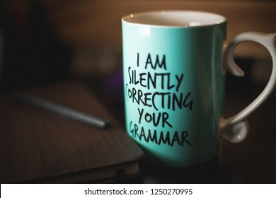 """""""I am silently correcting your grammar"""" coffee mug for comedy and education purposes. Turquoise mug on black ground with cozy background."""