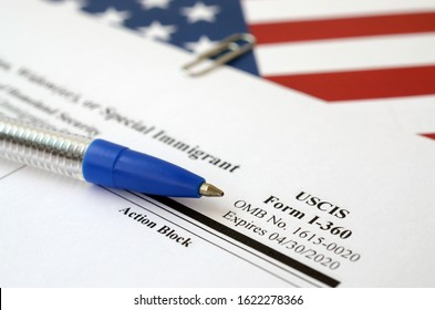 I-360 Petition for Amerasian, Widower or special immigrant blank form lies on United States flag with blue pen from Department of Homeland Security