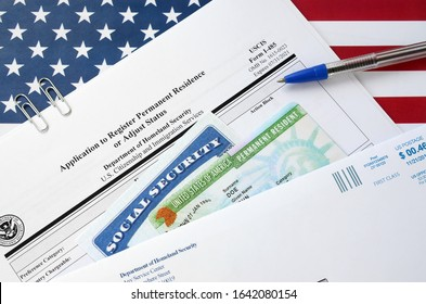 I-485 Application to register permanent residence or adjust status form and green card from dv-lottery with social security number lies on United States flag with USCIS envelope