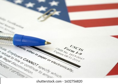 I-9 Employment Eligibility Verification blank form lies on United States flag with blue pen from Department of Homeland Security