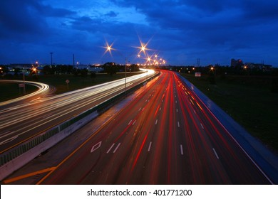 I-95 at Glades Road in Boca Raton, Florida Facing North in Twilight with Deep Dark Blue Sky Overhead, Time Exposure with White Headlights, Red Tail Lights and Orange Blinkers Creating Streaks
