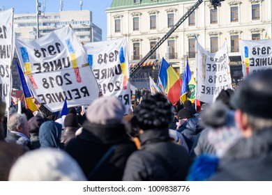IASI, ROMANIA - JANUARY 24, 2018: People with placards marching and celebrating on the main street at the national day of 100 years since unification of Romania, tricolor flag