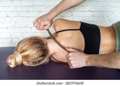 IASTM treatment, girl receiving soft tissue treatment on her neck with stainless steel tool