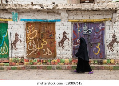 IBB, YEMEN - MAY 10, 2007: An unidentified woman walks in a street with graffiti. Modern day women of Yemen do not hold many economic, social or cultural rights.