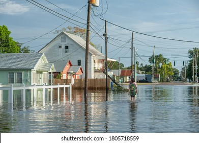 IBERIA PARISH, L.A. / USA - AUGUST 27, 2020: Canal street in Delcambre, during Hurricane Laura, two people walk along the flooded roads in town as the storm surge subsides.