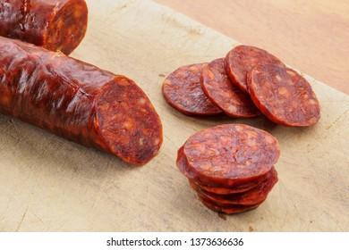 Iberian chorizo, Spanish chorizo or Spanish sausage cut into slices on a wooden board. Typical spanish dish