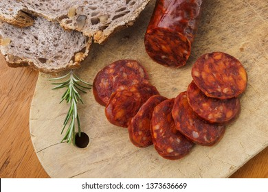 Iberian chorizo, Spanish chorizo ​​or Spanish sausage cut into slices on a wooden board with rustic bread