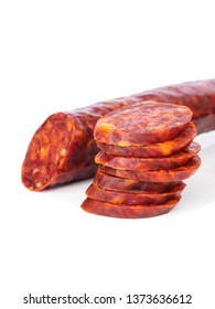 Iberian chorizo, Spanish chorizo ​​or Spanish sausage with its slices placed one on another on a white background with its reflection, typical tapa