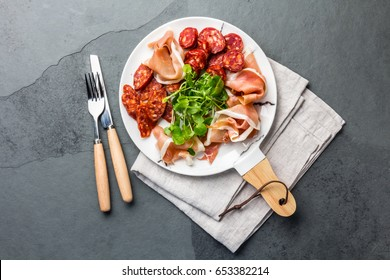 Iberian food. Spanish ham jamon serrano and salami on white marbled plate board. Slate gray background. Top view. Copi space. Antipasto