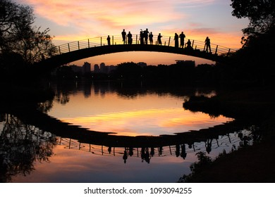 Ibirapuera Park. Awesome and colorful sunset by the lake. Beautiful sky reflections on the water. People gathered over the bridge to watch the golden hour miracle. Sao Paulo, Brazil