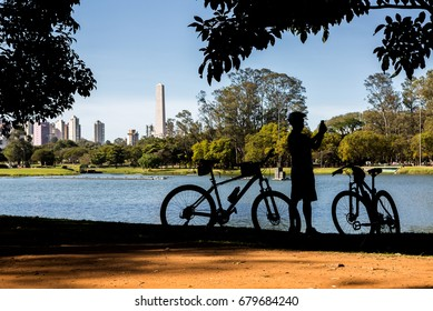 Ibirapuera Park, Sao Paulo, Brazil. Cyclist by the lake in Ibirapuera Park, Sao Paulo, Brazil, taking photos.