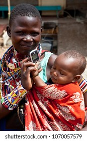 IBISIL, KENYA-DECEMBER 7, 2010: Unidentified Maasai woman with baby holds a cell phone while dressed in traditional clothing.