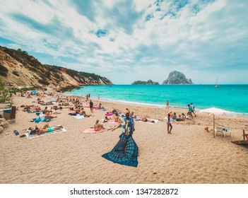 Ibiza, Baleares, Spain, June 2018. Numerous tourists on the beach of Cala d'hort, in front of the islets of Es Vedrá and Es Vedranell, on the hippy island of Ibiza, in spring.