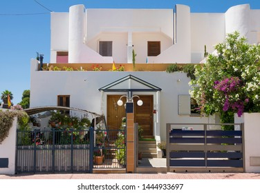 IBIZA, BALEARIC ISLANDS, SPAIN - JUNE, 2019: Two wooden different entrance doors of a traditional white Ibiza duplex house.