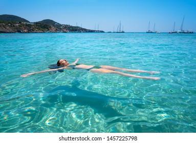 Ibiza bikini girl swimming clear water beach of Balearic Islands