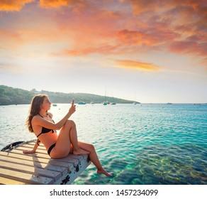Ibiza girl taking smartphone photos at Portinatx beach  pier in Balearic Islands