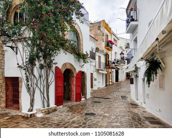Ibiza Island architecture. Charming empty cobblestone white-washed street of old town of Ibiza (Eivissa). Blooming ivy with red flowers on a house wall. Cloudy sky, no people. Balearic Islands. Spain