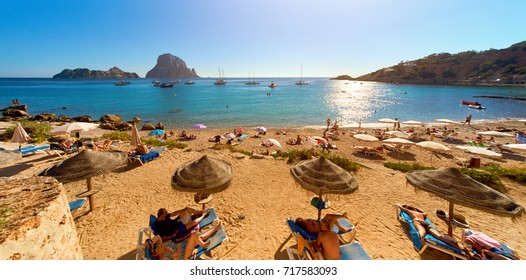 Ibiza Island, Spain - June 12, 2017: People at Cala d'Hort beach. Cala d'Hort in summer is extremely popular, beach have a fantastic view of the mysterious island of Es Vedra. Ibiza Island. Spain