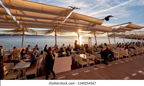 Ibiza Island, Spain - May 1, 2018: Crowd of calm people vacationers meet sunset at popular seafront place terrace of Savannah cafe, on West Coast of Ibiza. Glowing sun above,  Mediterranean Sea. Spain