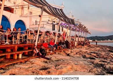 Ibiza Island, Spain - May 1, 2018: People meet the sunset at the seafront terrace of Cafe Del Mar. This place is famous for views to the sunsets lounge music clubbing. Ibiza, Balearic Islands. Spain