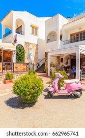 IBIZA ISLAND, SPAIN - MAY 18, 2017: classic pink Vespa scooter parking in garden of traditional restaurant in Sant Carles de Peralta village, Ibiza island, Spain.