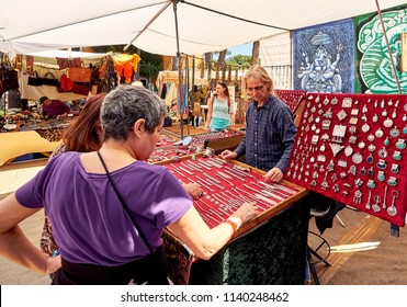 Ibiza Island, Spain - May 2, 2018: Seller and buyers at the Hippy market of Ibiza Island. Stall selling fashion accessories and silver jewellery with precious gems. Balearic Islands. Spain