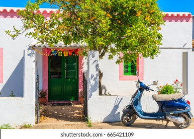 IBIZA ISLAND, SPAIN - MAY 20, 2017: classic Vespa scooter parking under lemon tree and traditional white housein Sant Carles de Peralta village, Ibiza island, Spain.