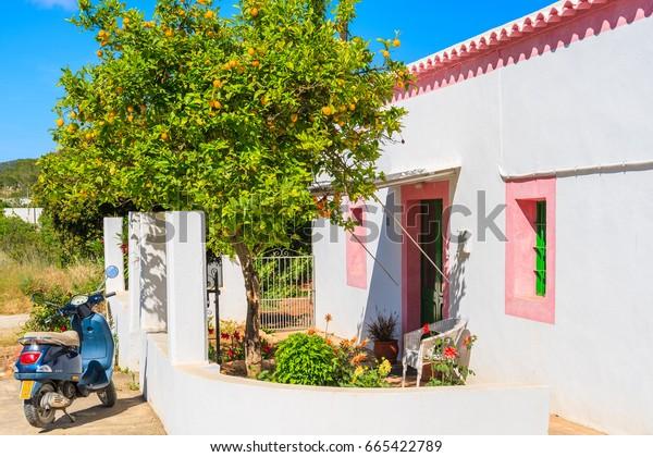 IBIZA ISLAND, SPAIN - MAY 20, 2017: classic Vespa scooter parking under lemon tree and traditional white housein Sant Carles de Peralta village, Ibiza island, Spain.