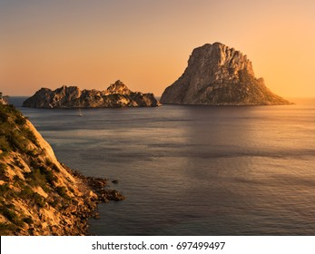 Ibiza, Spain. It is Vedrá at dusk, in summer. Cliff of Cala D'Hort boat and mediterranean sea