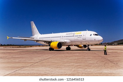 IBIZA, SPAIN, July 16 2018: A ground handler is waiving to the Vueling Airbus A320 at Ibiza International Airport in Ibiza, Spain.