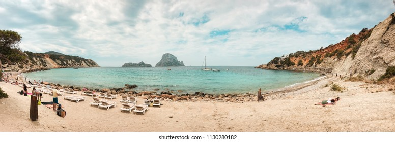 Ibiza, Spain, June 2018. Panoramic photograph of Cala D'Hort beach in Ibiza, Spain. People enjoying the beach and islets of Es Vedrá and Es Vedranell