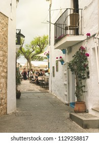 Ibiza, Spain, June 2018. Typical white streets of the Dalt Vila area. People resting in restaurant area and walking