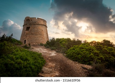 Ibiza, sunrise behind old stone tower, torre de Sal Rossa next to natural park Ses Salines, castle