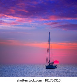 Ibiza sunset sun view from formentera Island with sailboat in Balearic Islands