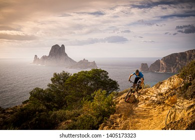 IBIZA,SPAIN - FEBRUARY 5, 2014. A man rides a mountain bike along a rocky trail on the west coast of Ibiza. Es Vedrá Island and the Mediterranean Sea are in the background.
