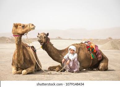 Ibri, Oman, 28th April 2018: bedouin kid with his camels on a countryside of Oman