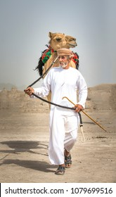 Ibri, Oman, 28th April 2018: men with his camel walking in a countryside of Oman