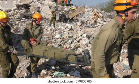 IBTIN, ISRAEL - DECEMBER 17, 2015: Israeli Homeland Security Soldier carry injured soldier on stretcher during earthquake rocket attack tsunami drill after digging through the rubble