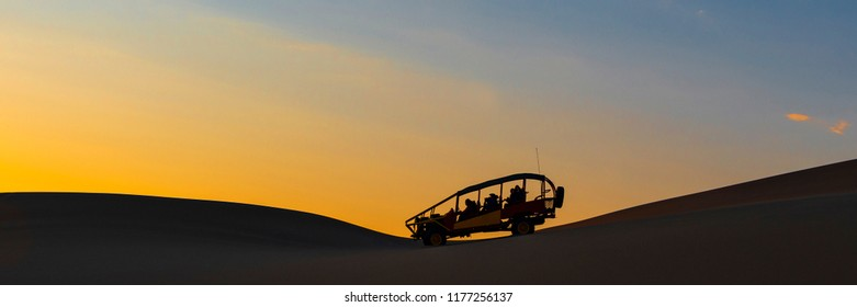 ICA, PERU - SEPTEMBER 2, 2018: Silhouette of a buggy with tourists at sunset in the coastal Peruvian desert between Ica and Huacachina, Peru.