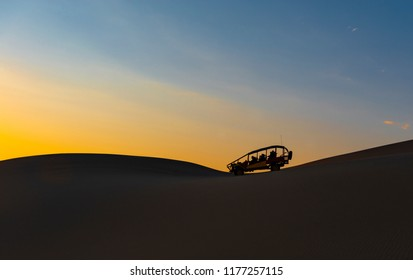 ICA, PERU - SEPTEMBER 2, 2018: The silhouette of a sand dune and buggy in the Peruvian desert of Ica near the Huacachina Lagoon at sunset in Peru.