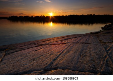 Ice age shaped beach rock in summer sunset