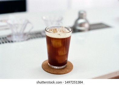ice americano on white table in coffee shop background.