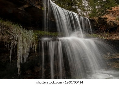 As ice begins to form on the edges, a waterfall at Oglebay Park in Wheeling, West Virginia splashes down over two tiers of rocky ledges.